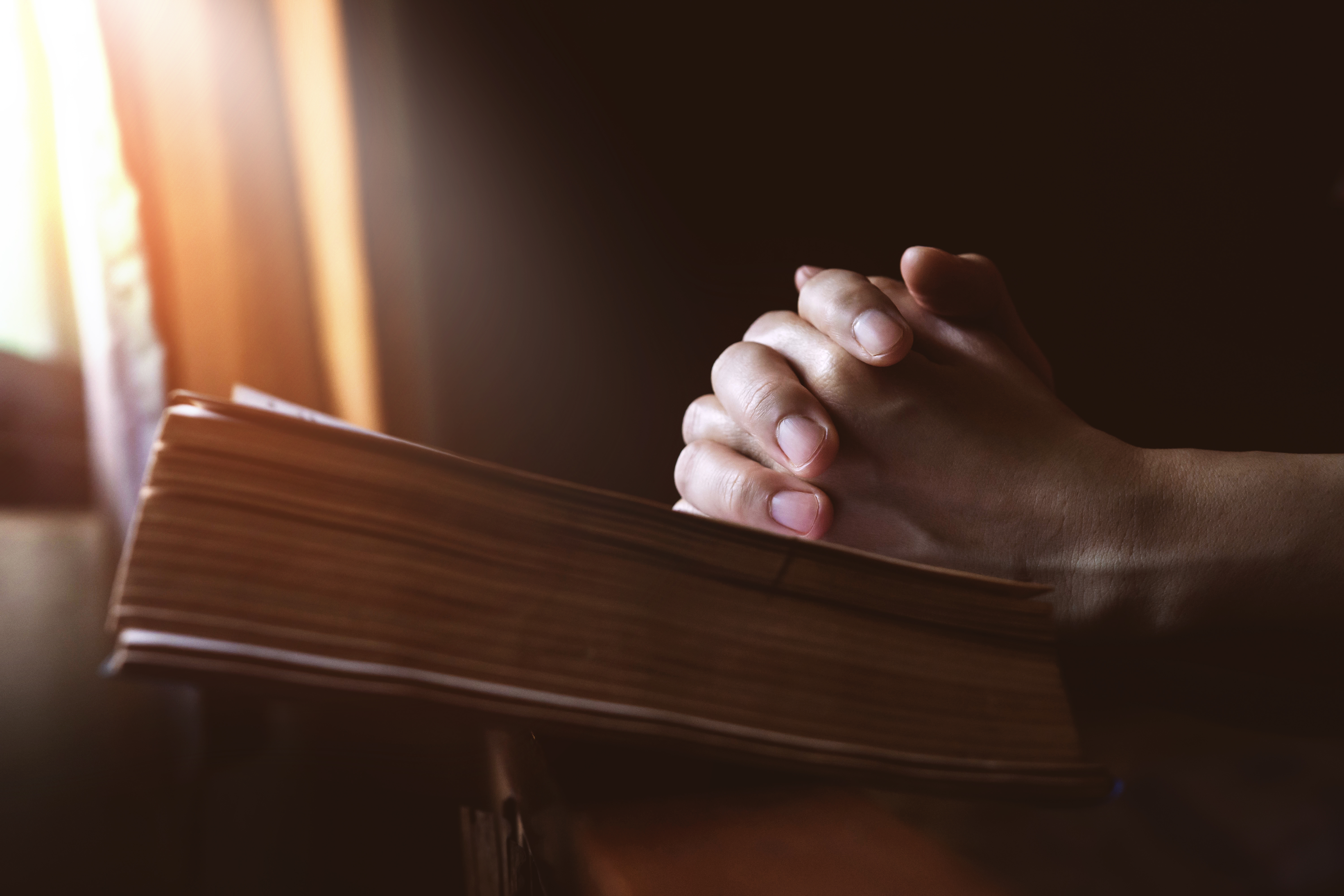hands-praying-on-holy-bible-beside-694585924