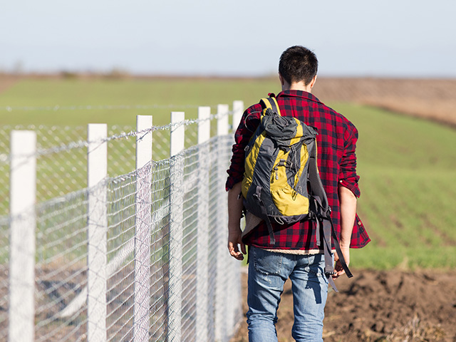 Young man with backpack walking beside fence 640 480px