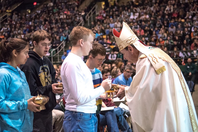 Students form Paul VI High School bring forth the gifts