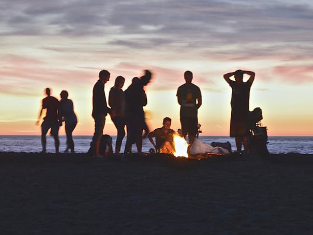 Young adults by fire on beach